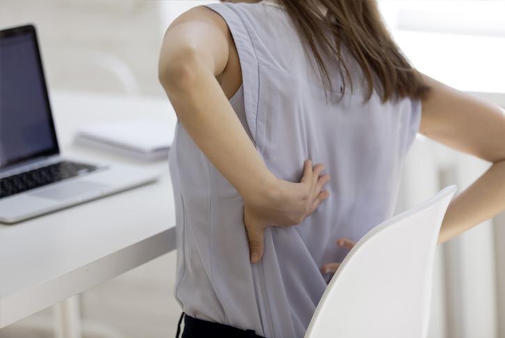 Frau mit Rückenbeschwerden im Sitzen