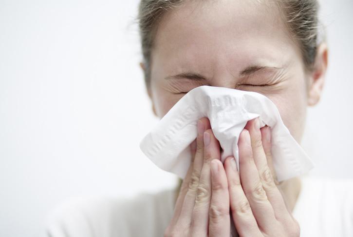 Frau schneuzt sich in ein Taschentuch. Allergie, Schnupfen, Rhinitis, Nase