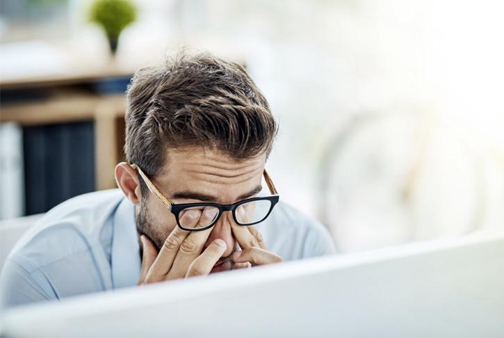Mann mit schmerzenden Augen, Kopfschmerzen vor einem Computerbildschirm