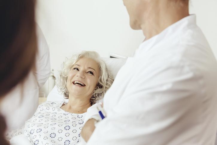 Arzt mit im Bett liegender Patientin im Gespräch