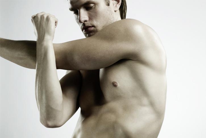 Mann macht Dehnübungen für Schulter und Arme