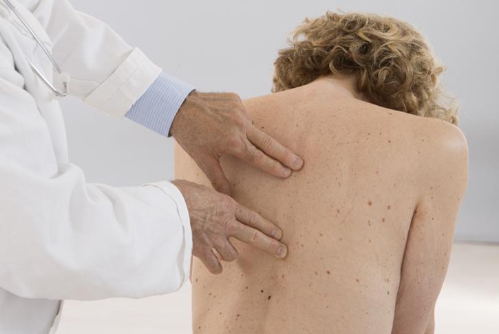 Arzt tastet Rücken einer Patientin ab