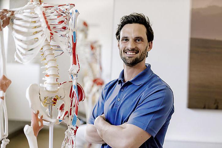 Physiotherapeut vor Modell des menschlichen Körpers